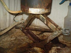 Garbage disposal held up with a car jack